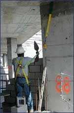 Masonry worker harnessed to building with safety straps